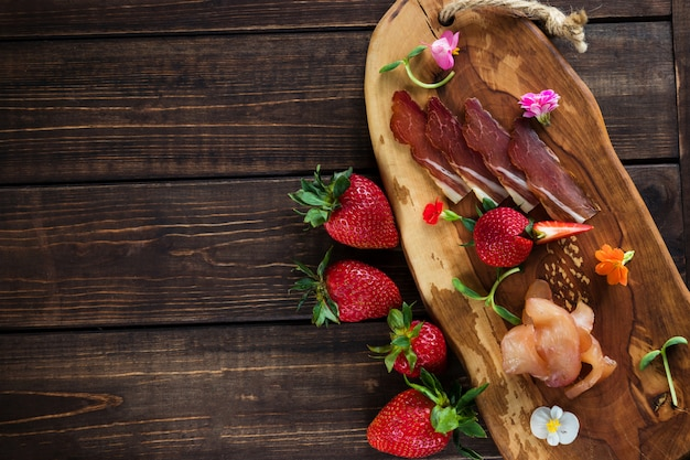Cold cuts on a plain background, wooden board, strawberries and micro greens. free place for text