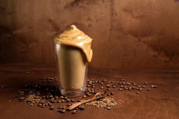 暗い背景の木の明確なガラスの冷たいダルゴンコーヒー