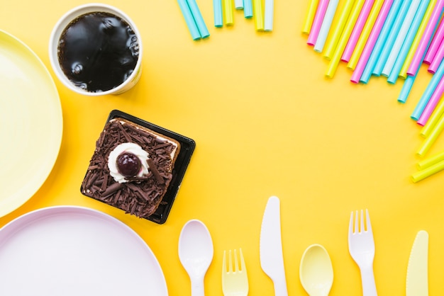 Cold drink; cake slice; empty plate; cutlery and straws on yellow backdrop