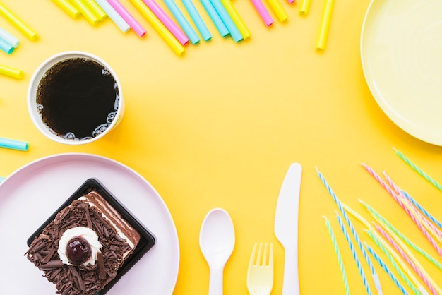 Cold drink; cake slice; empty plate; cutlery and straws