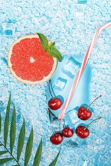 Холодный напиток. лед на голубом фоне выложен в виде стакана с трубочкой для коктейля и ломтиком грейпфрута