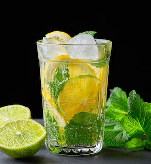 Cold drink made from pieces of lemon, lime and leaves of green mint in a glass with water drops