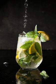 透明なグラスにモヒート、ミント、レモン、氷を入れて冷たい飲み物