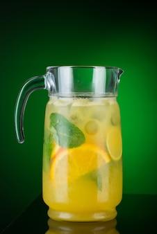 녹색 배경에 있는 디캔터에 있는 감귤류의 차가운 음료. 여름 열대 주스