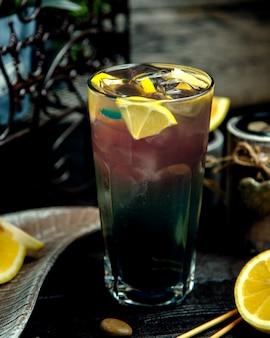 Холодный напиток с дольками лимона и со льдом на столе
