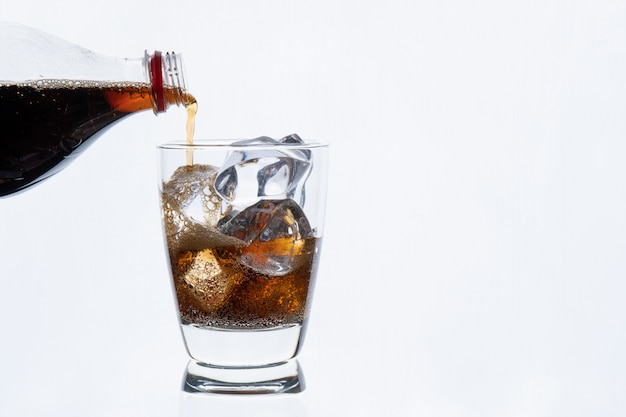 Cold drinking, pouring soda from bottle, glass of cola with ice for hot and summer drink isolated on white wall