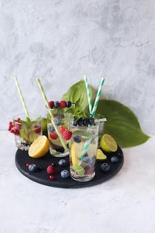 Холодные напитки из цитрусовых малины и листьев мяты черники и минеральной воды здоровый образ жизни