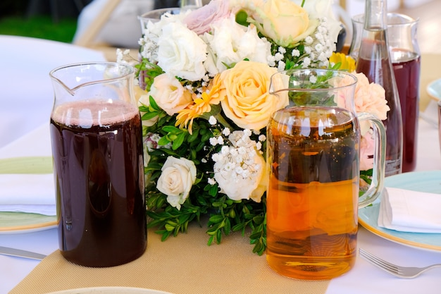 Cold drinks, juices and water on a banquet table decorated of flowers bouquet in a  restaurant.