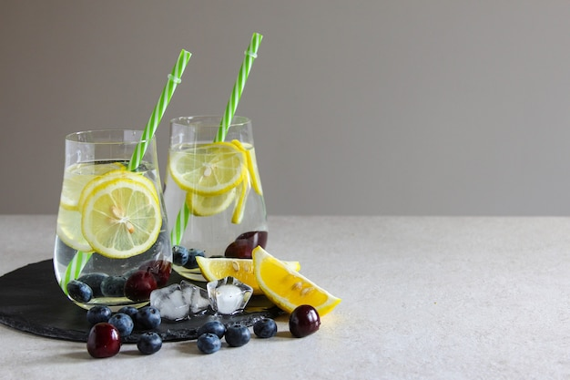Cold drinks in small bottles cherries and lemon lemonade mojito coctail summer iced drink