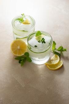 Холодные напитки с огурцом, лимоном и льдом. летний освежающий лимонад.