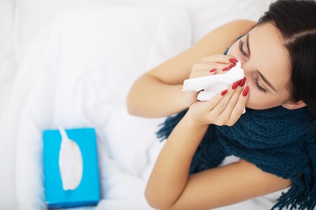 Cold and flu. portrait of ill woman caught cold, feeling sick and sneezing in paper wipe. closeup of beautiful unhealthy girl covered in blanket wiping nose. healthcare concept.