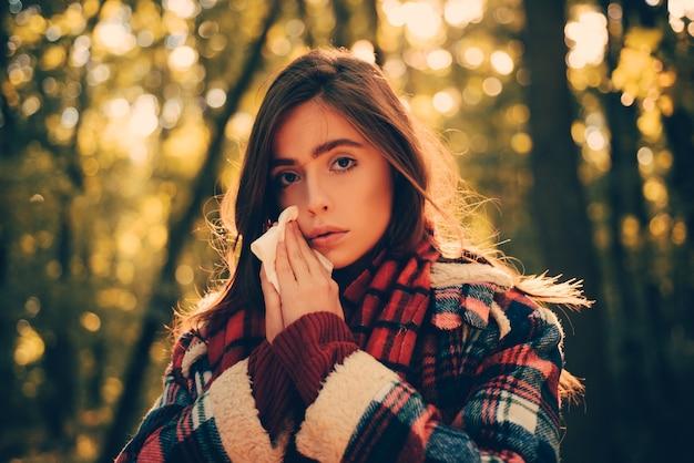 Сезон простудного гриппа, насморк. женщина с симптомами аллергии сморкается. портрет молодой женщины нюхает носовой спрей, закрывающий одну ноздрю. женщина с симптомами аллергии сморкается.