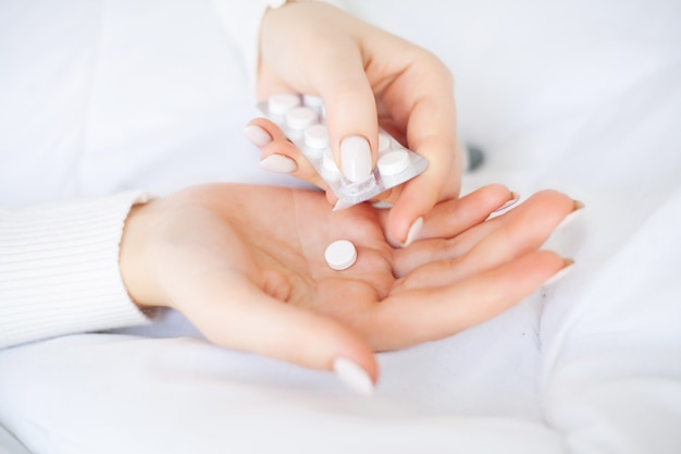 Cold and flu. woman hold pills in hand, lying on the bed.