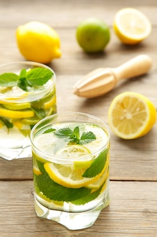 Cold fresh lemonade drink on a grey wooden background