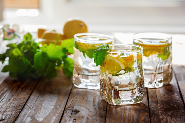 Cold fresh lemonade with lemon and mint on wooden background