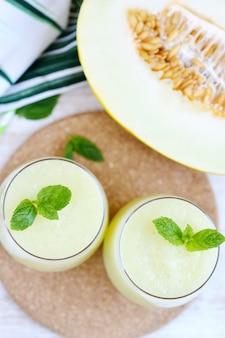 ガラス、夏の飲み物飲料、健康食品のコンセプト、鮮度、エキゾチックなフルーツのミントと冷たい新鮮なメロンのスムージー