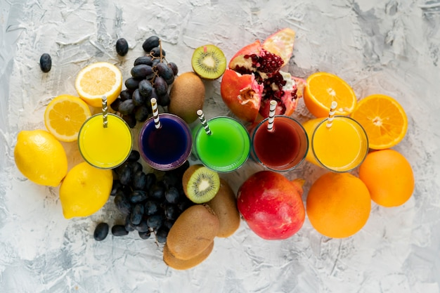 Cold fresh smoothie squeezed from different tropic exotic fruits such as grapes kiwi lemon orange and garnets