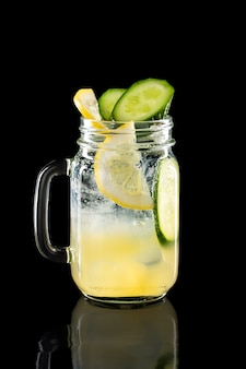 Cold fruit lemonade in mason jar isolated on black