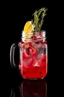 Cold fruit lemonade in mason jar isolated on black