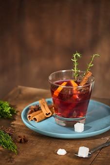 ガラスのカップにオレンジとレモンを入れた冷たいジンジャーティー。砂糖入りのお茶。装飾。シナモンとローズマリーのスパイス Premium写真