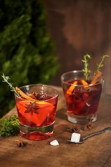 ガラスのカップにオレンジとレモンを入れた冷たいジンジャーティー。砂糖入りのお茶。装飾。シナモンとローズマリーのスパイス