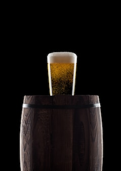 Cold glass of craft beer on old wooden barrel on black background with dew and bubbles