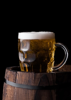 Cold glass of craft beer on old wooden barrel on black background