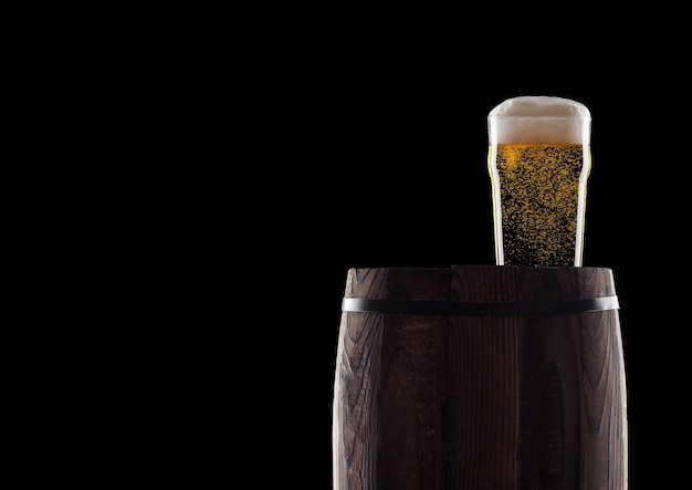 Cold glass of craft beer on old wooden barrel on black with dew and bubbles.