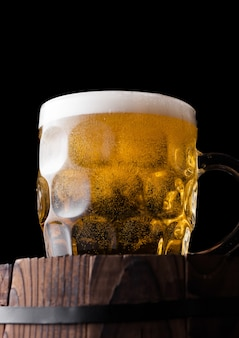 Cold glass of craft beer on old wooden barrel on black