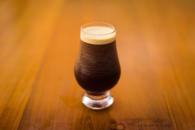 A cold glass of dark beer on a wooden surface