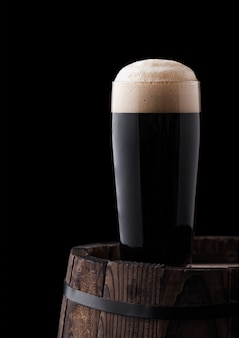 Cold glass of dark stout beer on wooden barrel on black background
