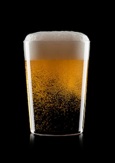 Cold glass of lager ale craft beer with foam and bubbles on black background