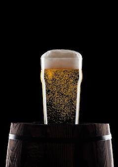 露と泡と黒の背景に古い木製の樽にクラフトビールの冷たいガラス
