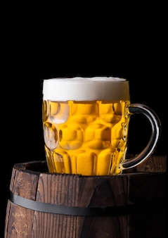 黒の背景に古い木製の樽にクラフトビールの冷たいガラス
