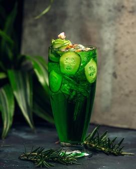 Холодный зеленый напиток в стакане с нарезанными ломтиками огурца