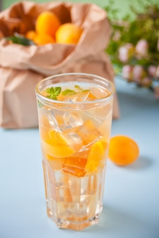 Cold homemade apricot ice tea with ice cubes and mint