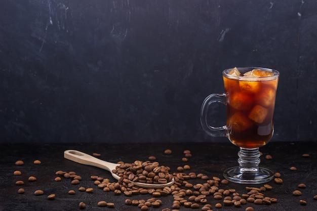 散らばった穀物と暗い背景に対してガラスの冷たいアイスコーヒー