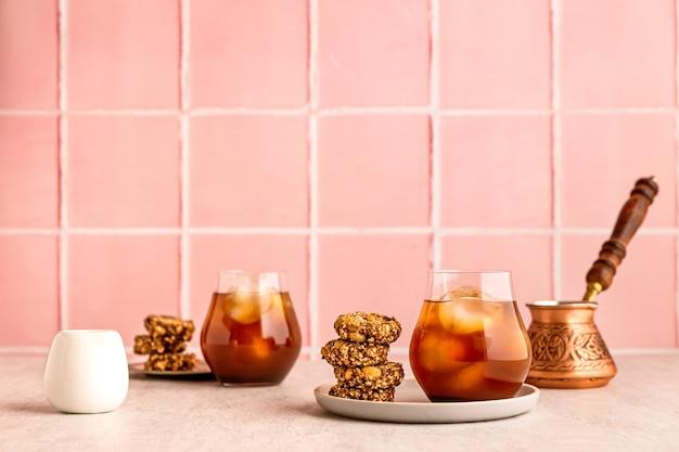Холодный кофе со льдом в стакане, подается с овсяным печеньем. турка и белый молочник. теплый свет и яркое изображение, розовый кафельный фон
