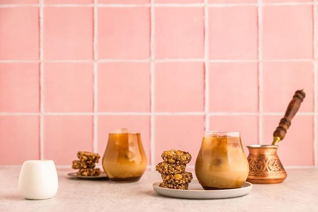 Холодный кофе со льдом с молоком в стакане, подается с овсяным печеньем. турка и белый молочник. теплый свет и яркое изображение, розовый кафельный фон