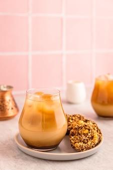 Холодный кофе со льдом с молоком в стакане, подается с овсяным печеньем. турка и белый молочник. теплый свет и яркое вертикальное изображение, фон из розовой плитки