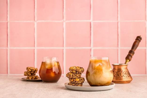 Холодный кофе со льдом с молоком в стакане, подается с овсяным печеньем. турка. теплый свет и яркое изображение, розовый кафельный фон