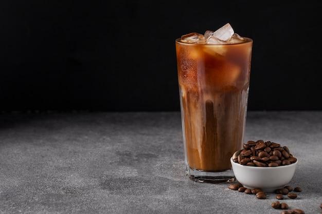 Холодный кофе со льдом с молоком на темном столе кофейные зерна, летний напиток