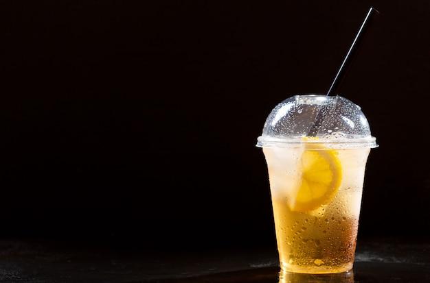 Холодный чай со льдом с лимоном и соломой в пластиковом стакане на вынос на темном фоне