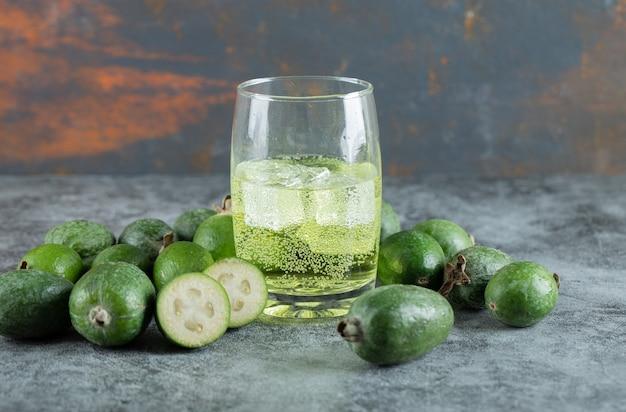 大理石のテーブルに冷たいジュースとフェイジョアの果物。