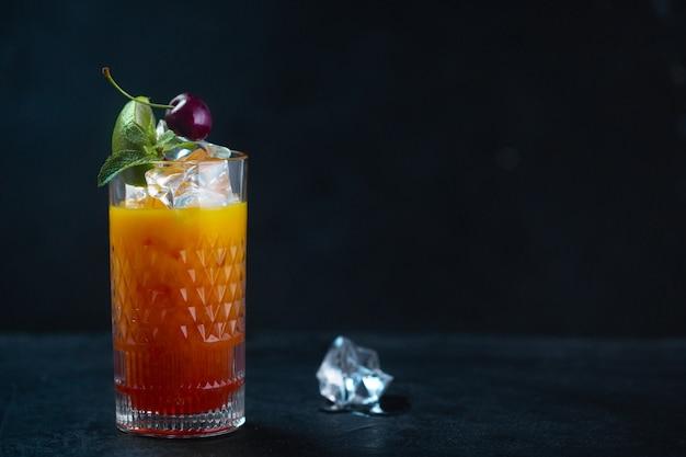 Холодный сок со льдом, мятой и вишней в стакане