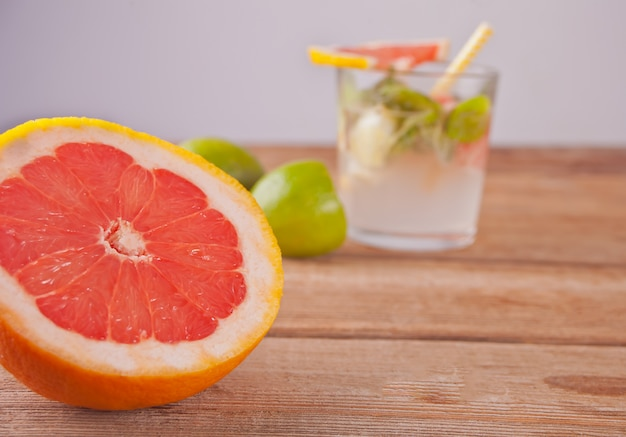Cold juice with pink grapefruit, lime and mint leaves on wooden table