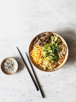 Cold korean kuksi soup with vegetables, scrambled eggs, beef and noodles in a bowl and chopsticks. top view