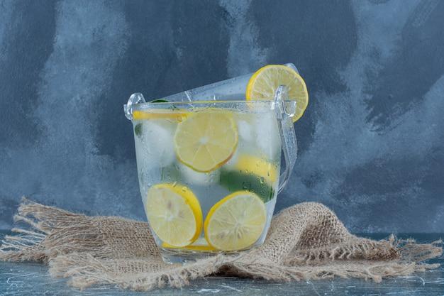 Bevanda fredda al limone sull'asciugamano, su sfondo blu. foto di alta qualità