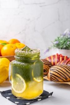 白いテーブルにレモンで飾られた冷たいレモン蜂蜜抹茶