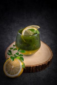 木製のまな板にレモンで飾られた冷たいレモン蜂蜜抹茶